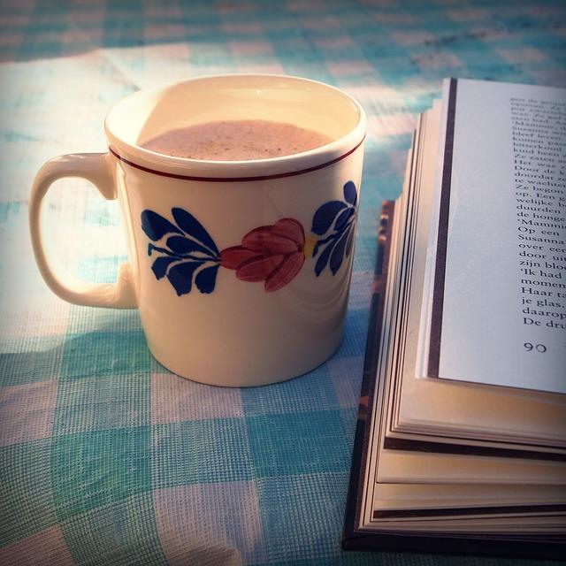 Mug of coffee next to open book.